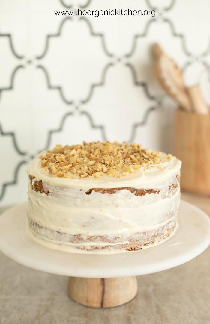 Gâteau aux carottes avec glaçage au fromage à la crème garni de noix hachées sur plaque à gâteau