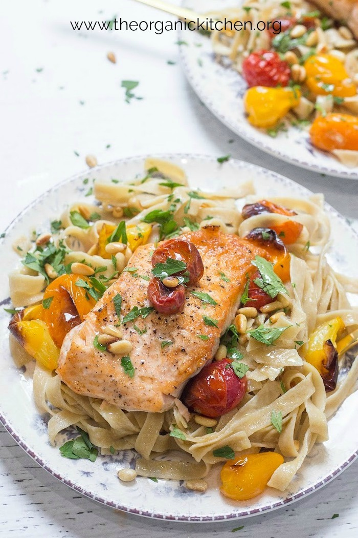 Two plates of Crispy Salmon with Blistered Tomatoes and Pasta on blue and white plates