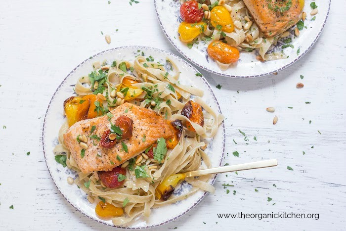 Two plates filled with Crispy Salmon with Blistered Tomatoes and Pasta with gold fork