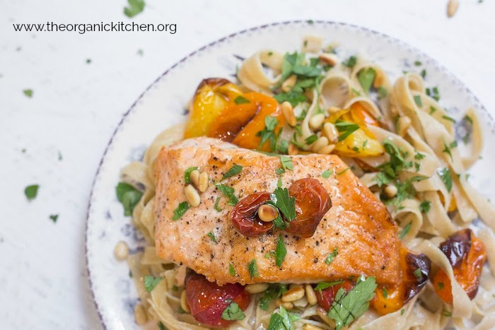 A single piece of Crispy Salmon with Blistered Tomatoes and Pasta on a white and blue plate