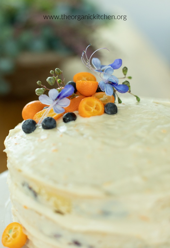 A close up of the toppings on an Orange Blueberry Cake: kumquats, blueberries, and flowers