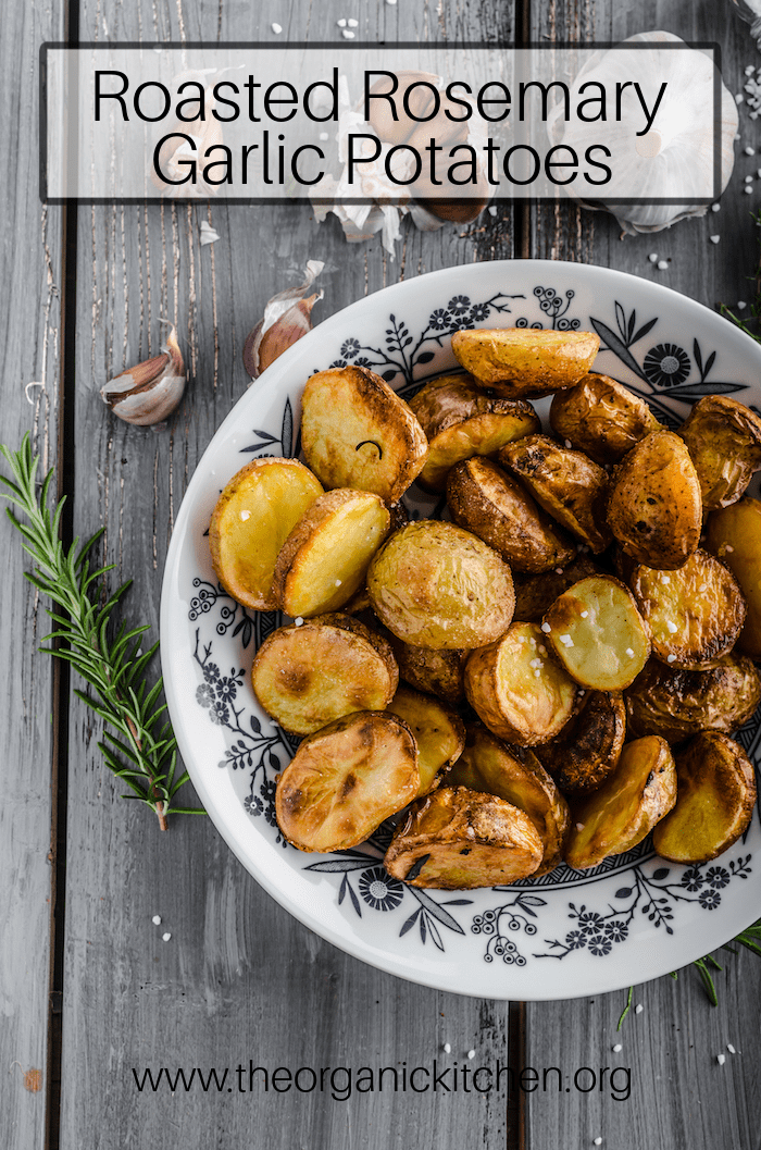 Whole30 Roasted Potatoes (with Rosemary Garlic Option) in a black and white bowl on gray wood surface surrounded by rosemary springs and garlic