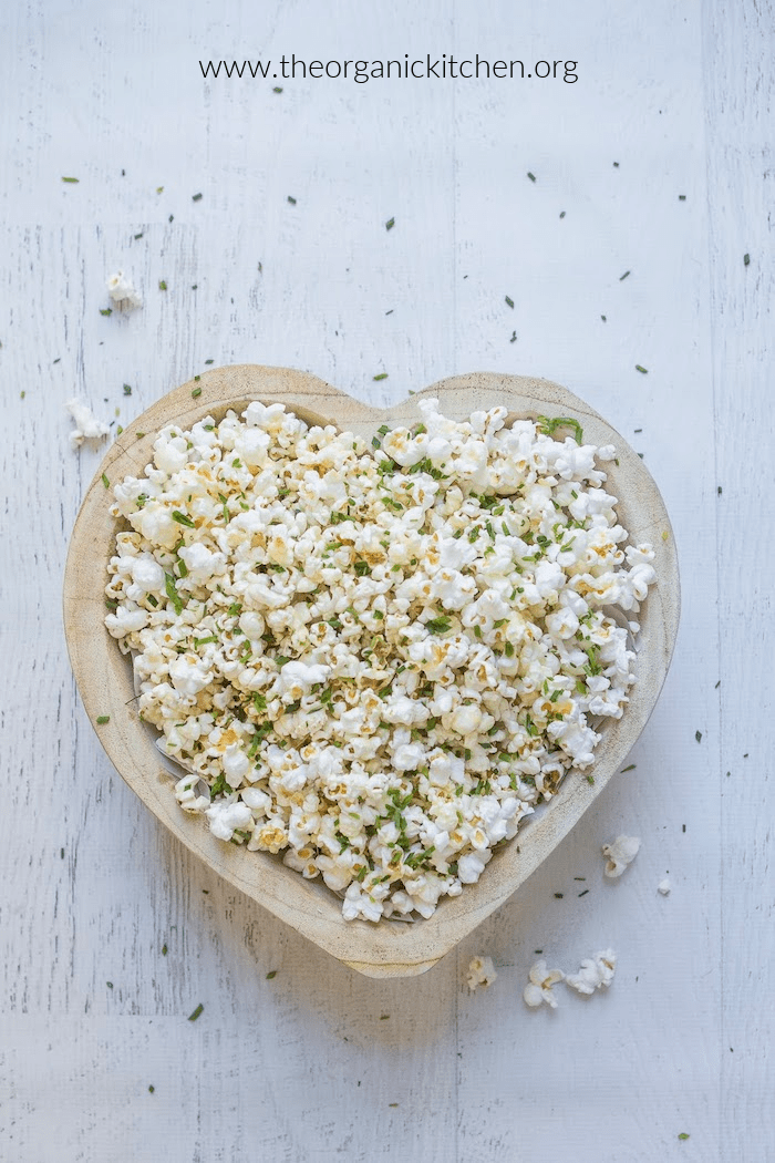 Parmesan Chive Popcorn in heart shaped bowl on white surface scattered with popcorn and chives