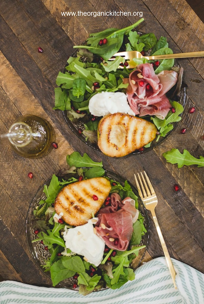 Two plates of Grilled Pear and Prosciutto Salad with gold forks and green and white dish towel at bottom of frame