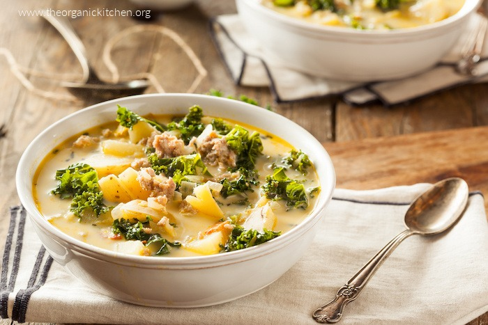 Zuppa Toscana (with Dairy free option) in a white bowl set on linen with a silver spoon