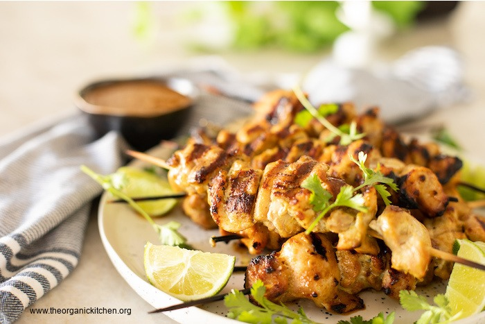 Chicken Satay with Sweet and Spicy Sauce garnished with lime and cilantro