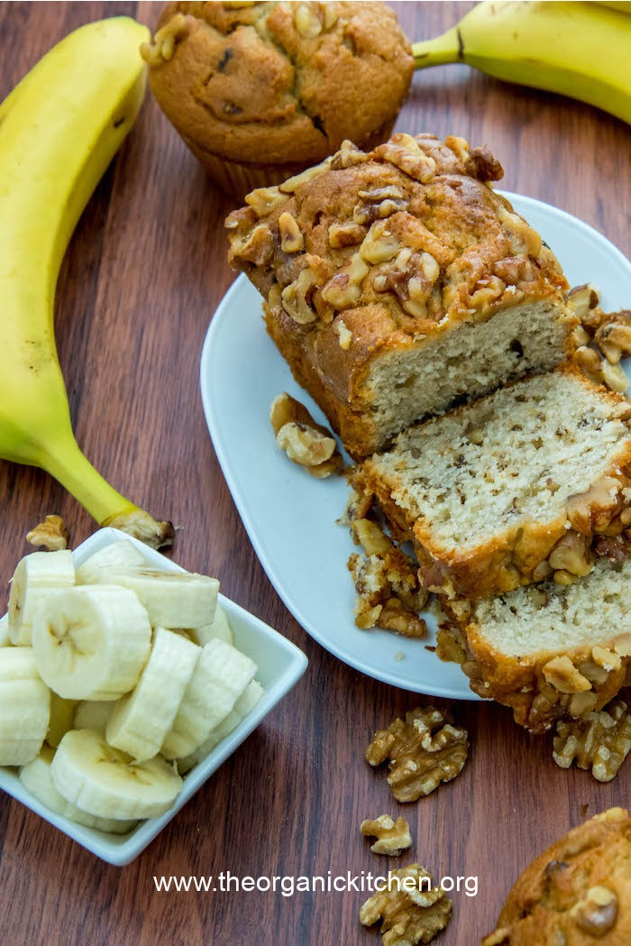 Banana Nut Bread or Muffins (gluten free option) on white plate surrounded by sliced bananas and walnuts