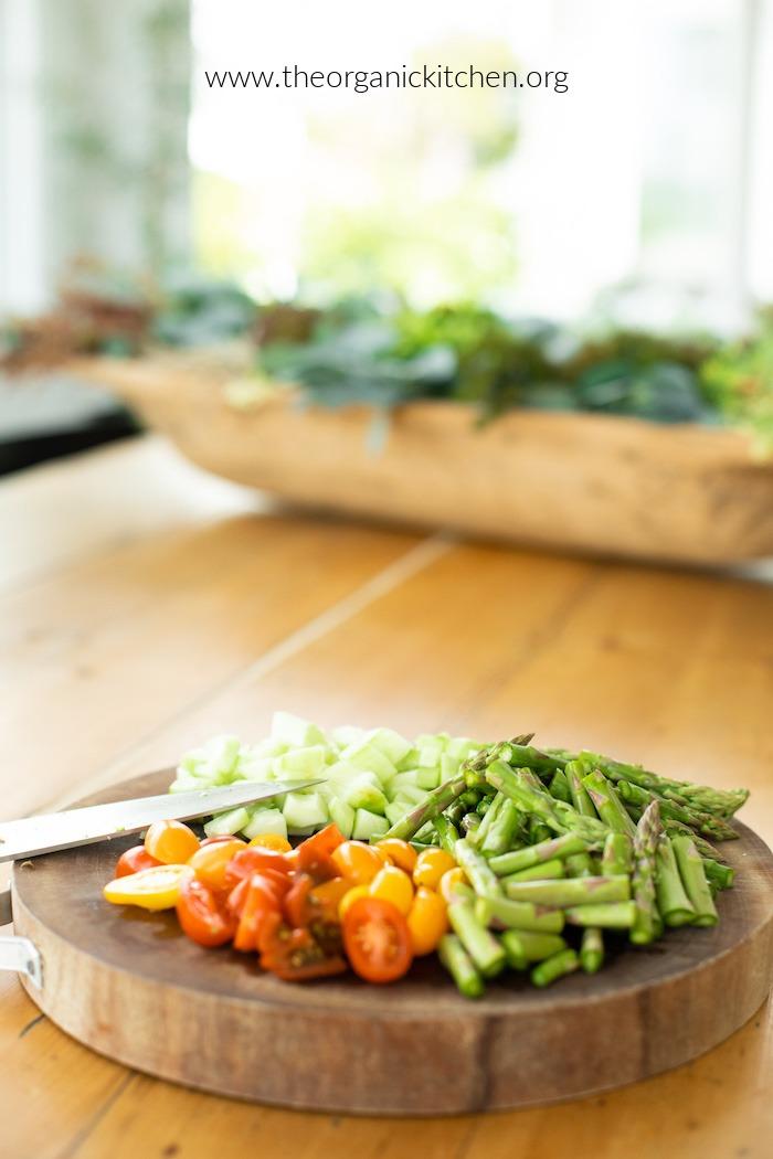 Ingrédients pour salade de pâtes aux légumes verts et aux asperges sur une planche à découper
