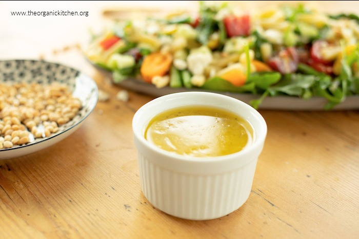 A white ramekin with lemon vinaigrette for Pasta Salad with Greens and Asparagus