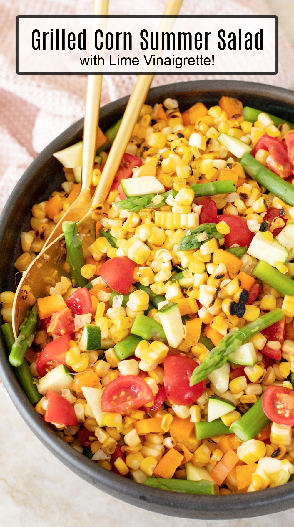 Grilled Corn Summer Salad in black bowl with gold serving spoons