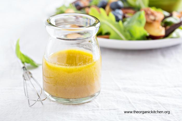 Vinaigrette au miel dans un petit pot à utiliser sur une salade d'abricots et de bleuets grillés