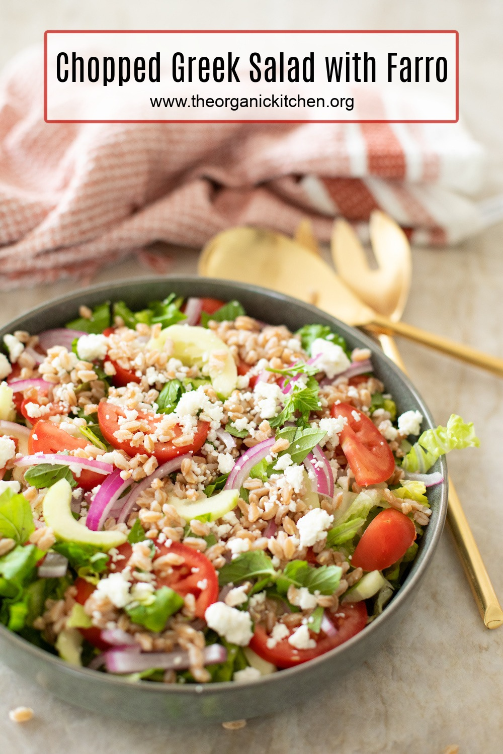 Chopped Greek Salad with Farro in a grey bowl with gold serving spoons