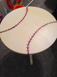 Draw black lines on the table at an angle to create the curves of the baseball then add red lines to create the stitching of a baseball