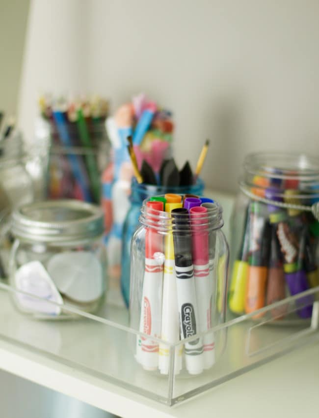 How to organize craft supplies with mason jars. Crayons are stored in mason jar, along with markers, pencils, paint brushes, and colored pencils. Embellishments are also stored and everything is contained in an acrylic tray #drawingsupplies #organization