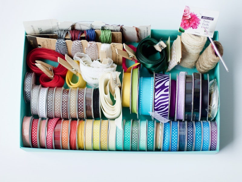 Ribbon storage in a box tip with the ribbons all color coded as a way of how to organize craft supplies. #ribbonstorage #organized