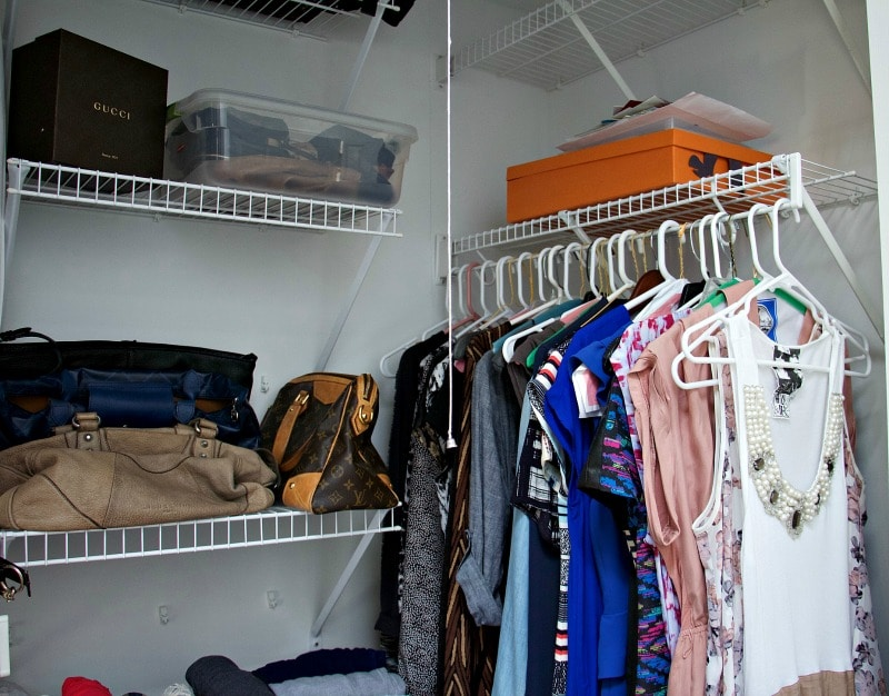 Organized closet with purses on shelf and dresses on hangers