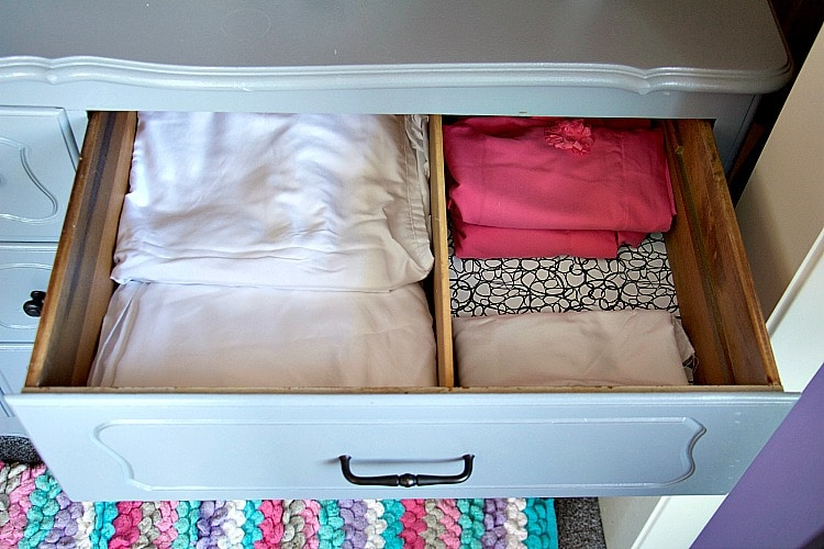 Open kid's drawer with organized sheets and pillow cases