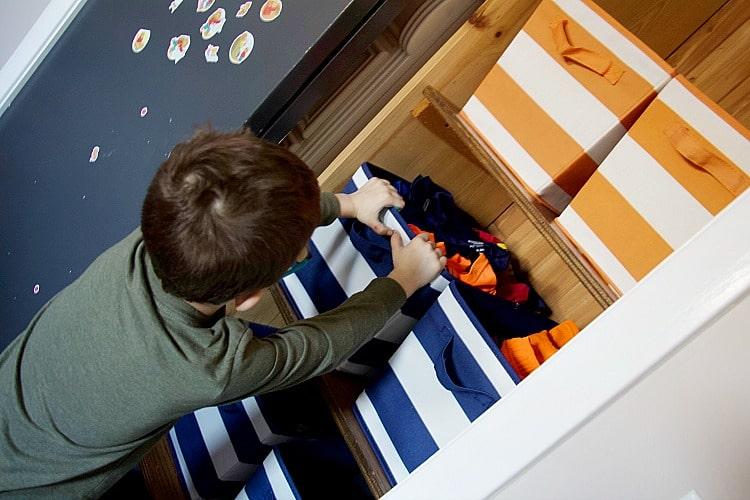 child putting away kids laundry in bin