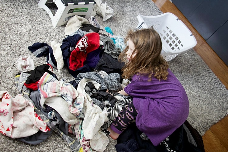 four year old sorting clothes in giant clothing pile looking for kids laundry