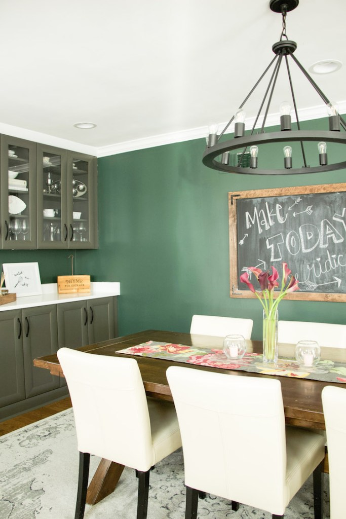 Dining area in open concept kitchen with dark hunter green paint against grey cabinets and wooden accents #kitchendecor #diningroom #darkpaint
