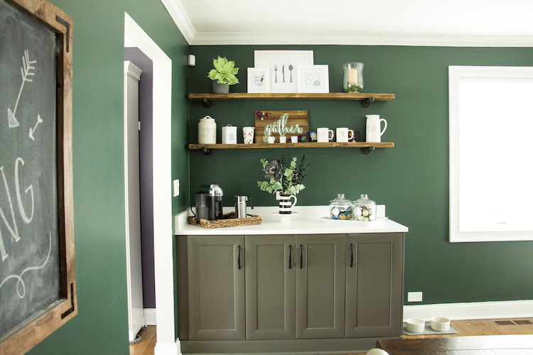 Wooden open shelving against a dark green wall in a kitchen as a coffee station. #kitchendecor #modernfarmhousedecor