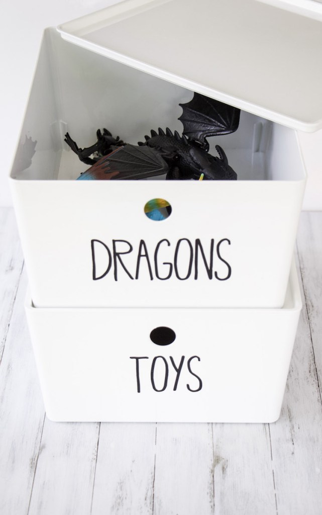 "looking inside two white stacked bins with black lettering that say ""dragons"" with dragons from the movie How To Train Your Dragon 3 inside"