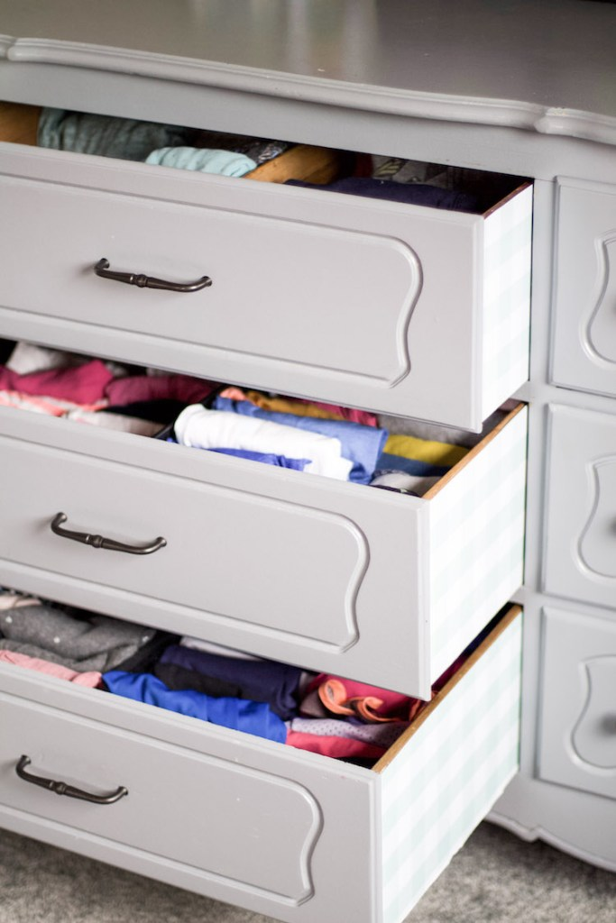 dresser drawers pulled out with shelf line on the outside in a sky blue gingham patteren