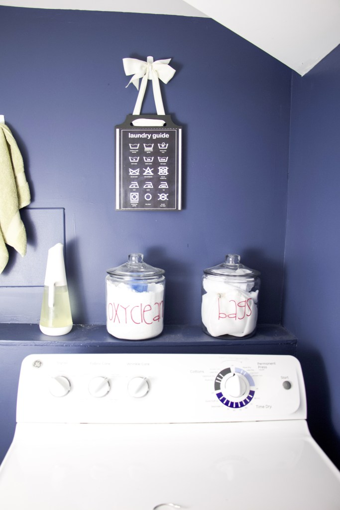Navy blue laundry room with glass jars and vinyl labels on each jar to demonstrate laundry room storage ideas