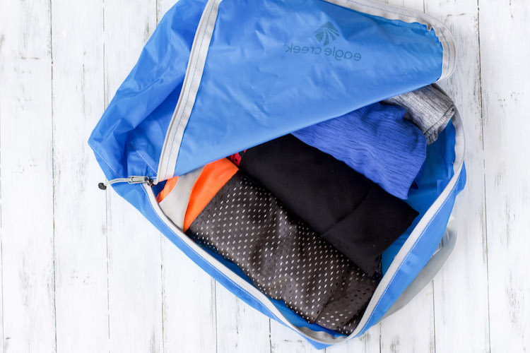 rolled up clothing in packing cubes with travel packing list