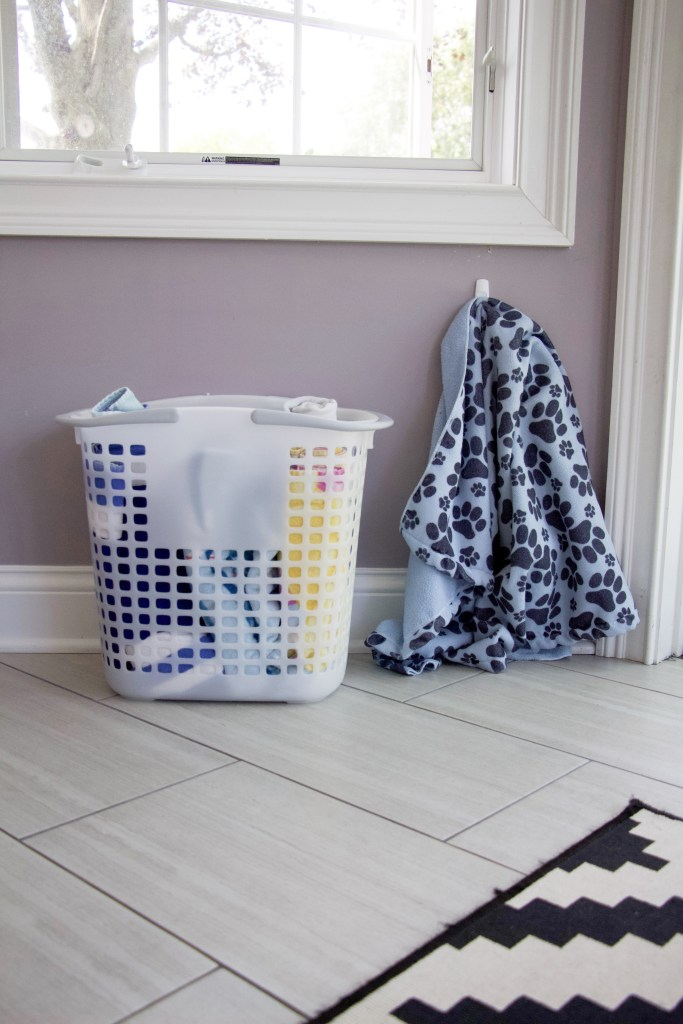 tote with rolled beach towels next to back door to demonstrate towel storage ideas #towelstorage