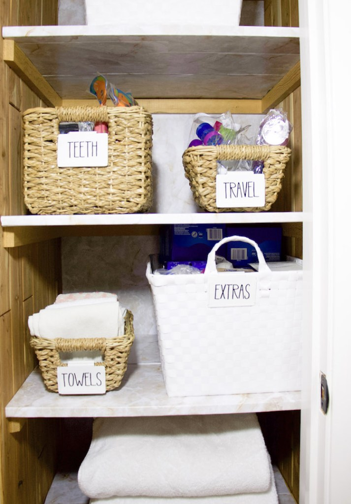 Folded towels, bins with clips for storing items inside a linen closet with marble shelf liner #organized