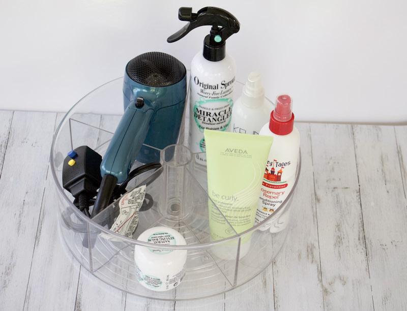 turntable with bathroom supplies include hair sprays and hair dryer #bathroomorganization