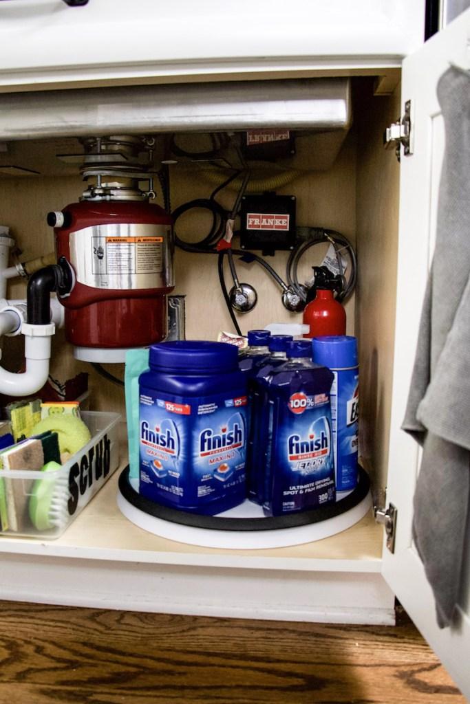 under kitchen sink turntable with cleaning supplies and dishwasher detergent #kitchenorganization