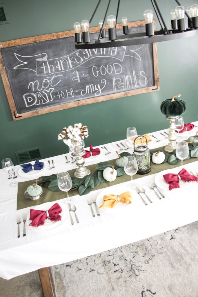 thanksgiving table decor with pumpkins, candle pillars, and chalkboard