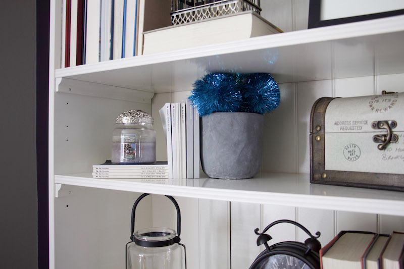 shelf decor using blue candles and pom poms