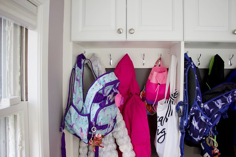 Daughter's jackets and backpack in mudroom section #organization