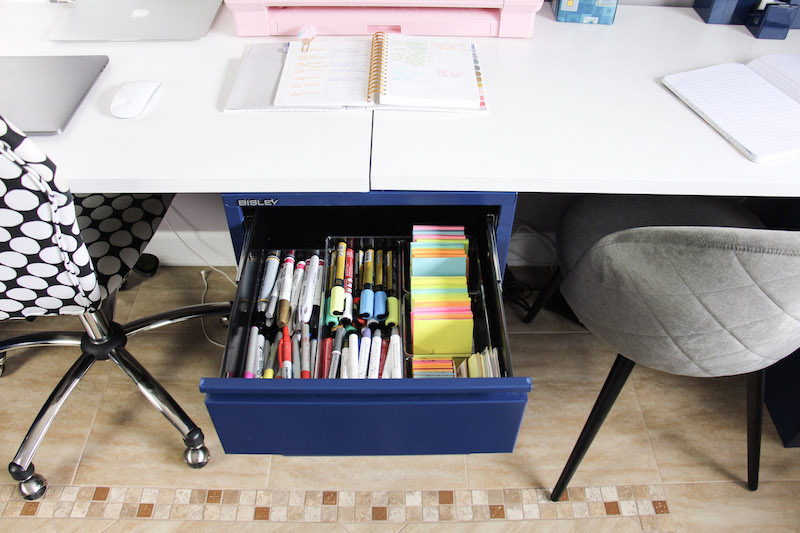 desk drawer with post it notes and sharpie markers
