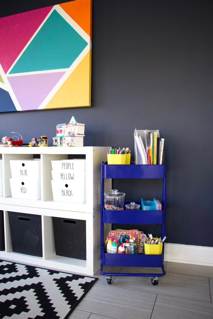dark blue paint in playroom next to art cart and ikea kallax storage for toys