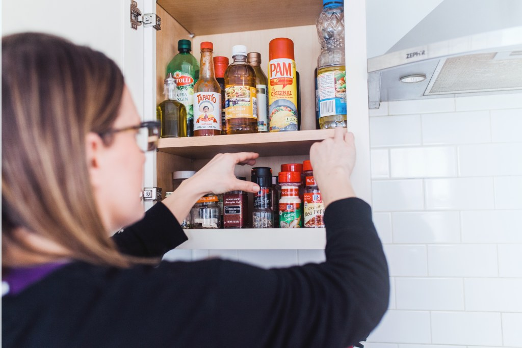 the organized mama decluttering kitchen cabinet
