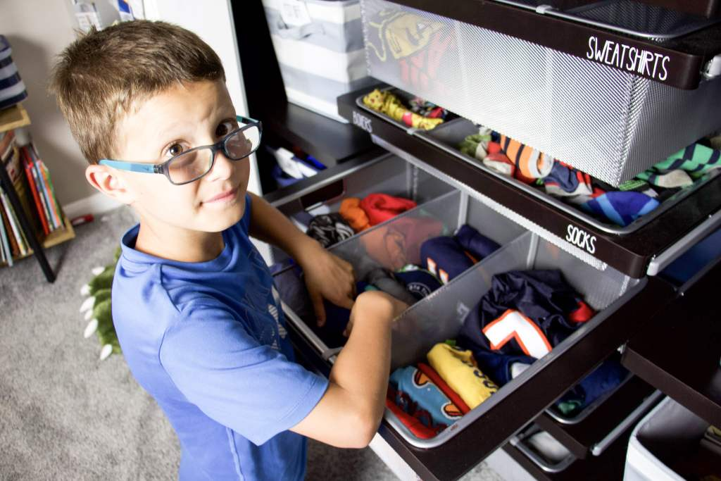 boy putting clothing into closet drawers with file folded clothing