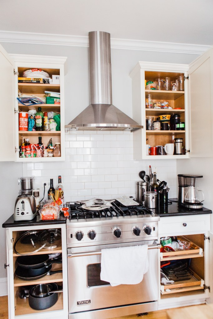 kitchen stove and cabinets with doors open to messy shelves