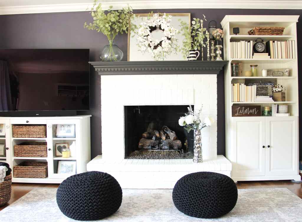 tv on stand next to white fireplace with a bookshelf to the right and two black poufs in front of the fireplace