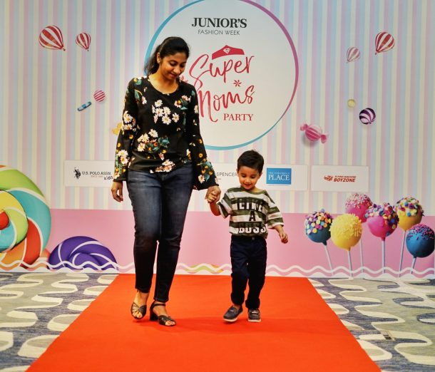 A kid dressed up in USPA T-shirt walks the ramp with mom at Super Moms Party - Junior's Fashion Week 2018