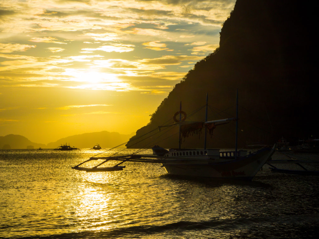 sunset view with boat in marimegmeg beach el nido palawan