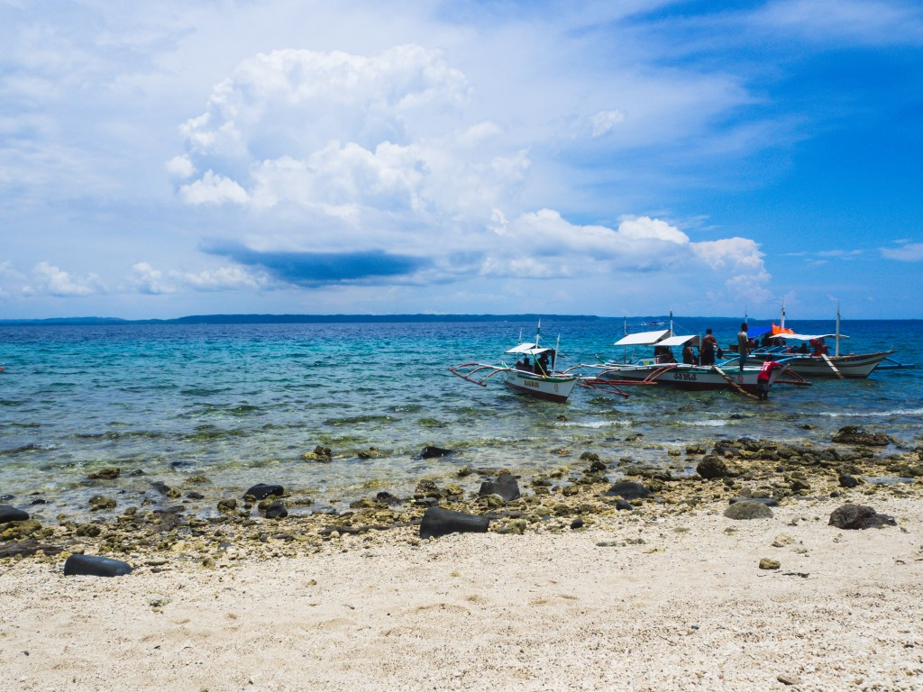 local boat in the shore in the blue waters of animasola island masbate