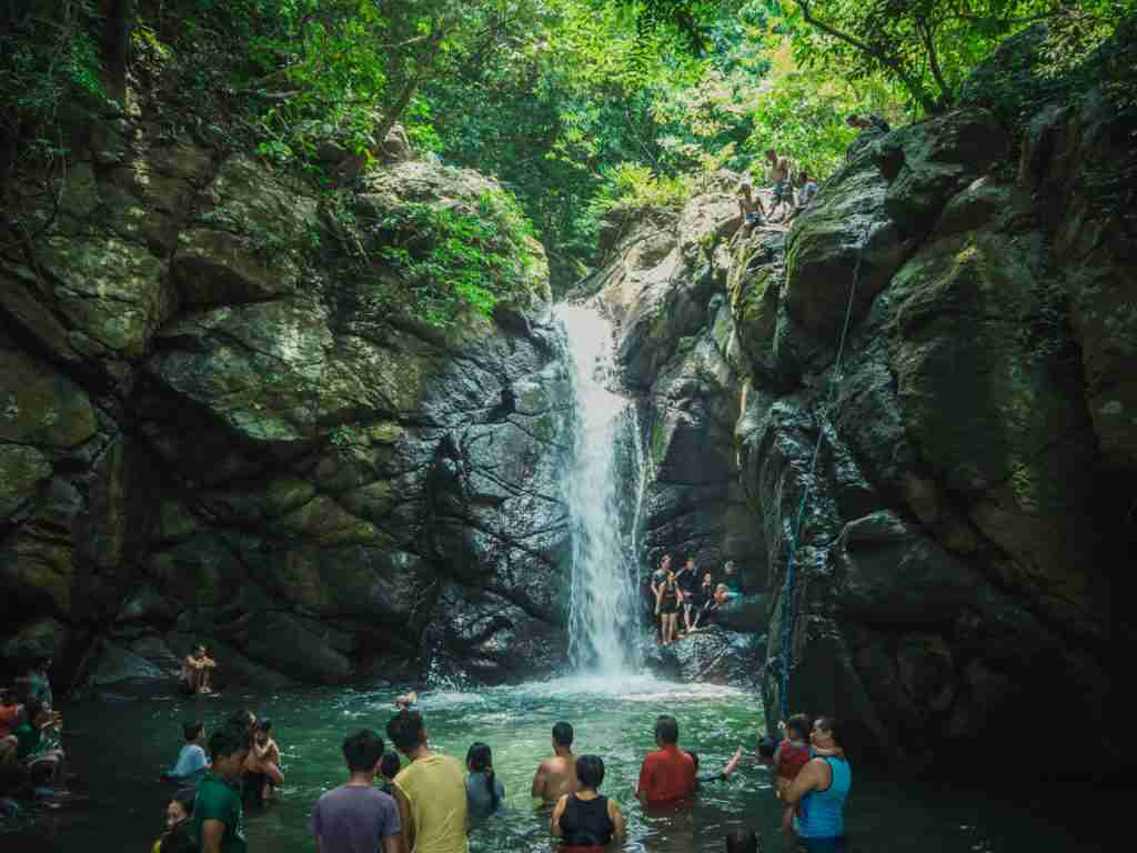 Nonok falls in Real Quezon with people swimming and cliff diving