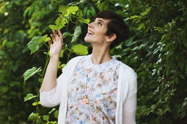 hannah is wearing a pastel floral peter pan collar blouse, a short white cardigan, and a pink flower necklace. her hair is styled in a short pixie cut. she's standing in greenery.