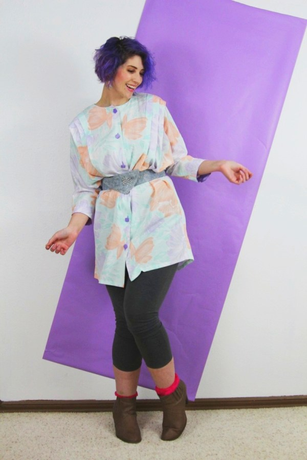 1980's fashion outfit: pastel tunic, gray leggings, violet curly hair, acid washed belt