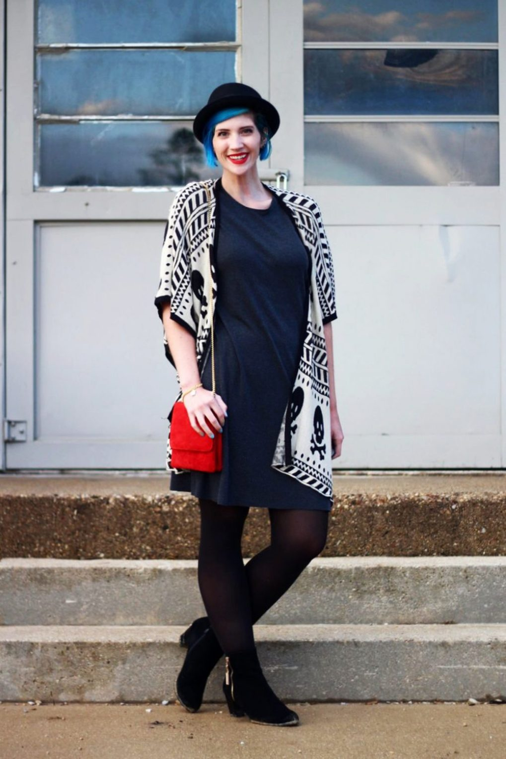 Outfit: Wearing a cardigan with a skull pattern, thrifted gray t-shirt dress, red purse, red lipstick, blue hair, black pork pie hat, black tights, black booties