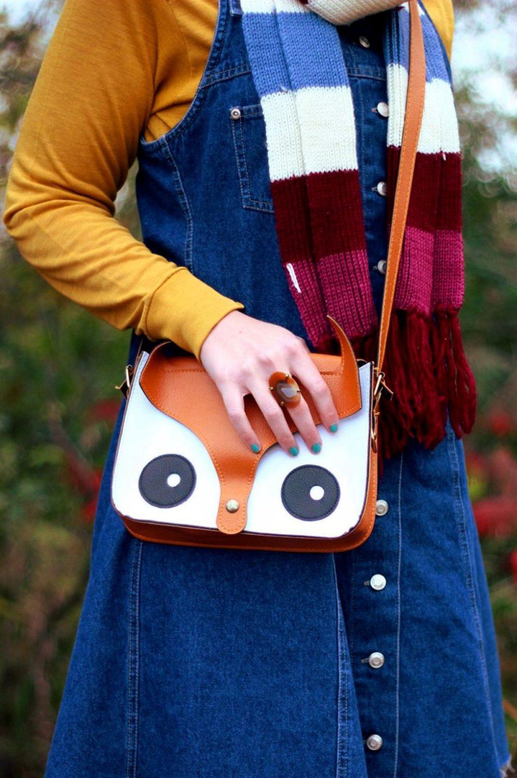 Outfit details: Mustard yellow turtleneck, denim overall dress, multi-colored striped scarf, orange fox handbag